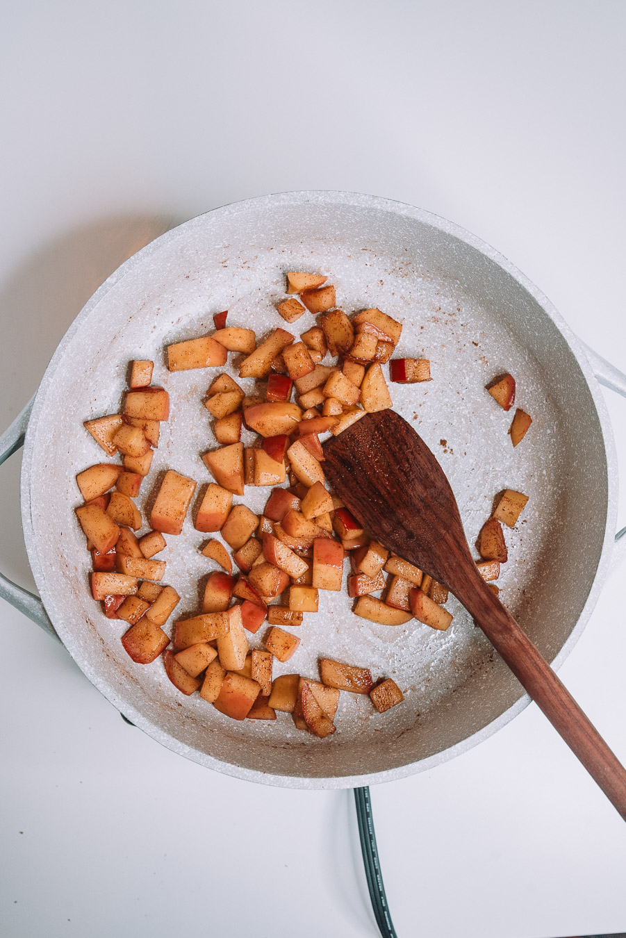 A skillet with sautéed apples on a white table