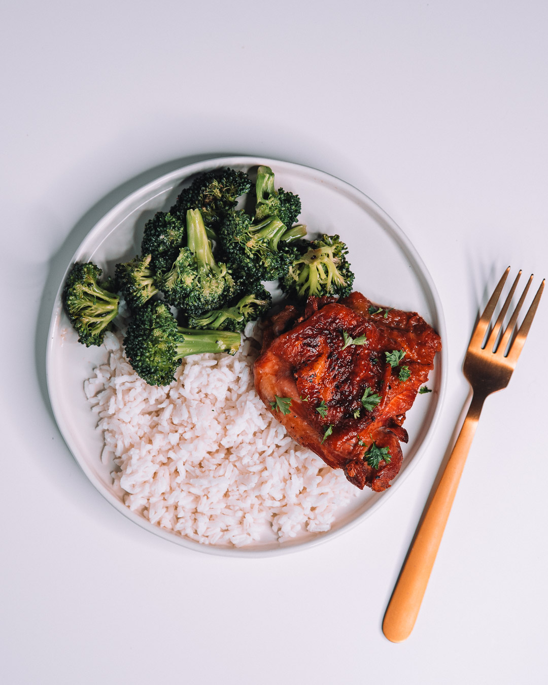 Instant Pot Honey Garlic Chicken on white round plate with a bed of white rice and freshly roasted green broccoli with gold fork.
