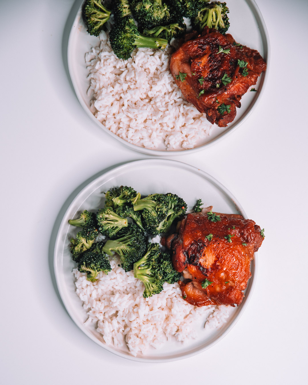 Instant Pot Honey Garlic Chicken on white round plate with a bed of white rice and freshly roasted green broccoli.
