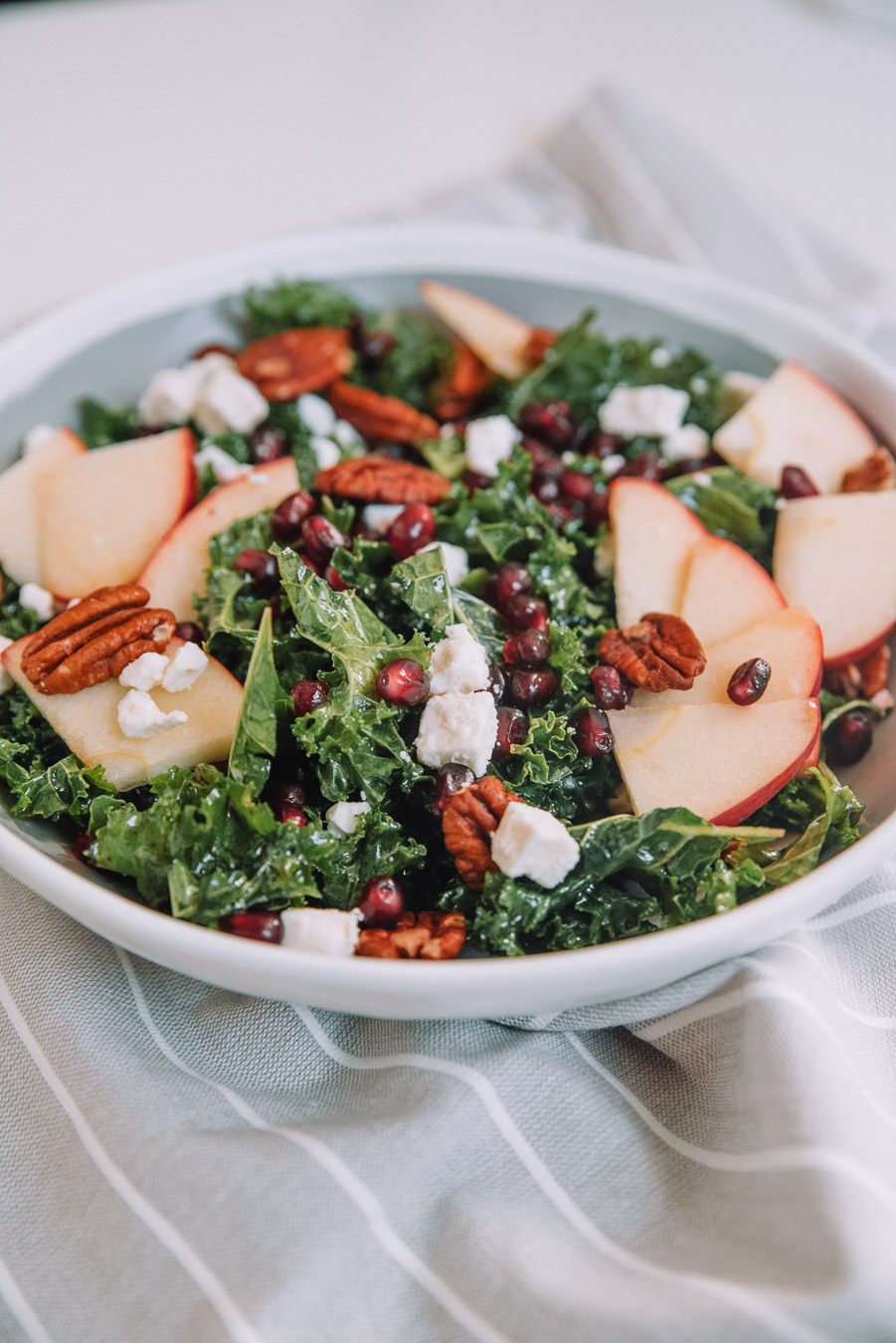 Kale Apple Salad with Pomegranate Dressing sprinkled with feta cheese crumbles and pecans in a bowl.